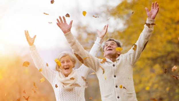Dos adultos mayores celebrando al aire libre