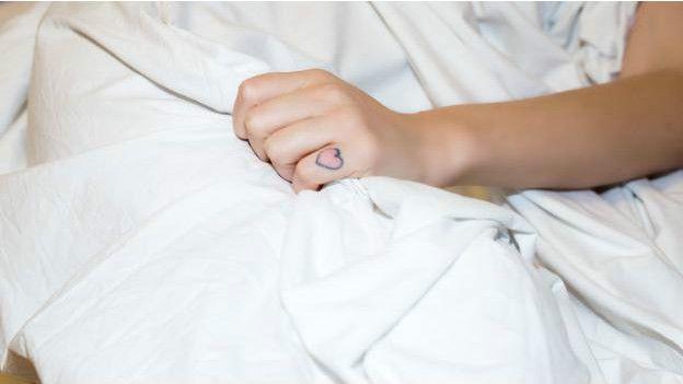 Una mano con un tatuaje que agarra una sábana