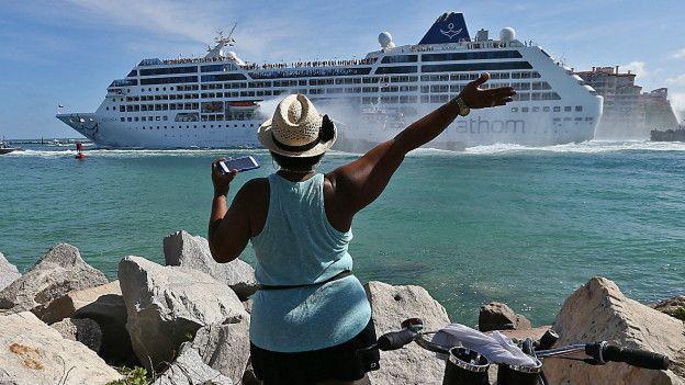 Una mujer despide el crucero desde tierra.