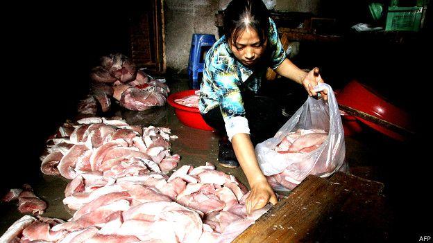 Mujer recogiendo carne en mal estado en Fuzhou, en la provincia de Fujian en 2005