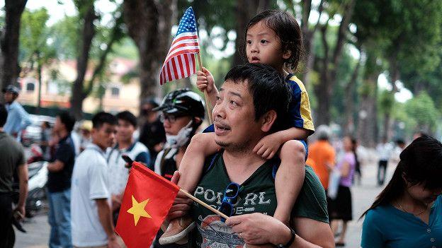 Вьетнамец с дочерью на плечах и с флажками