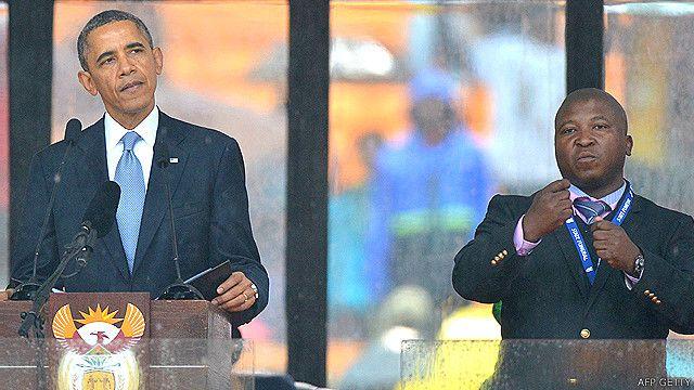 Thamsanqa Dyantyi (der.), intérprete de lenguaje de signos durante el servicio religioso en memoria de Nelson Mandela, junto a Barack Obama