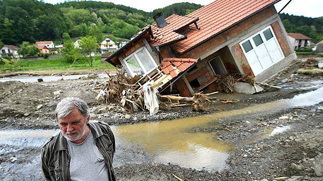 Hombre frente a su casa destruida por los deslaves en Krupanj, en Serbia