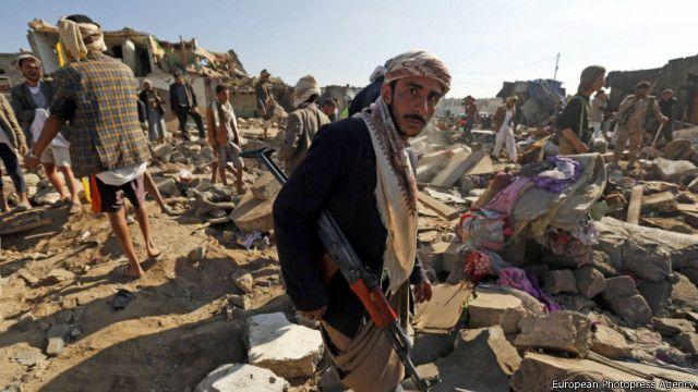 Повстанец-хусит у развалин домов после авиаударов коалиции во главес с  Саудовской Аравии