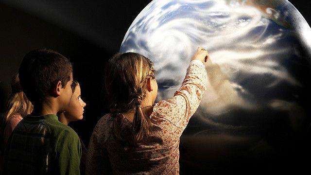 Schoolchildren looking at a globe