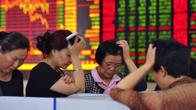 چین کی سٹاک مارکیٹ میں چند خواتین پریشان کھڑی ہیں