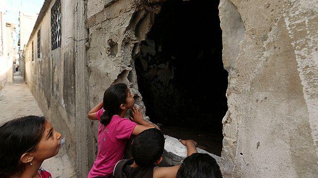 فلسطینی بچے ایک حملے سے ہونے والا نقصان دیکھ رہے ہیں