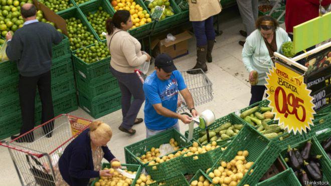 Clientes escogen mercadería en un mercado de frutas y verduras de Brasil.