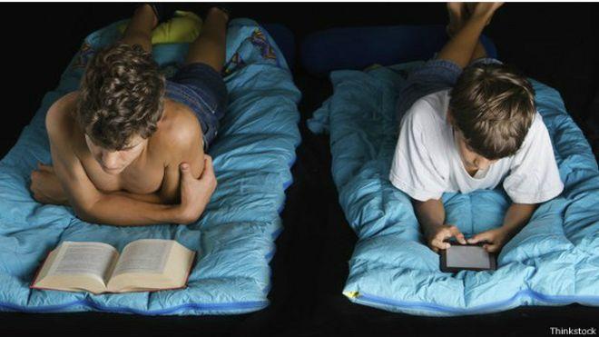Un joven leyendo un libro y un joven leyendo un libro electrónico, antes de dormir