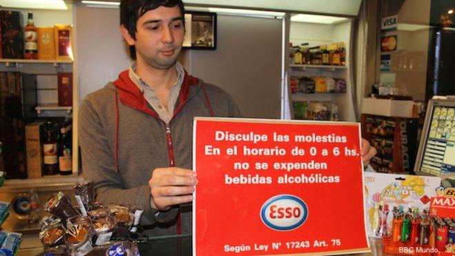 Un vendedor de una tienda en Uruguay muestra un cartel sobre la ley que prohíbe la venta de bebidas alcohólicas entre la medianoche y las 06:00 horas.
